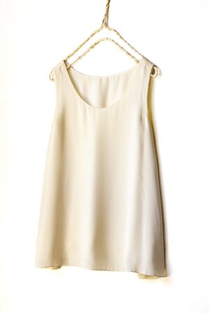 light beige or white tank top hanging on a hanger in a white wall.Close up