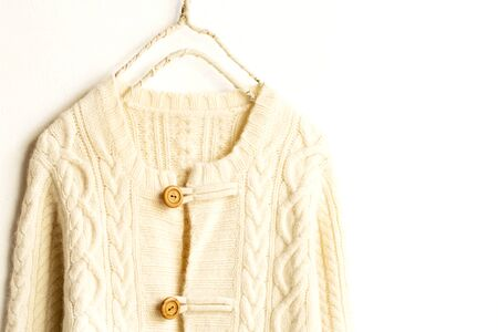 Beautiful, luxurious, a whole knitted cardigan in light beige on white background.