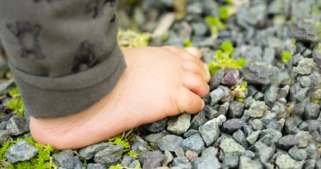 Close up of the one foot of the child walking on over gravel and copy space.