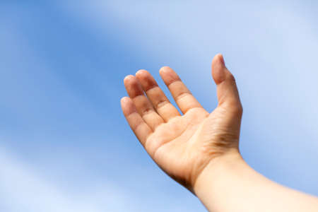 Woman's or man's hand turned up to the blue sky and copy space. Stock Photo