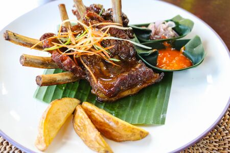 Roasted pork ribs with potato with sauce in white plate. Indonesia style roasted pork ribs. Food concept.