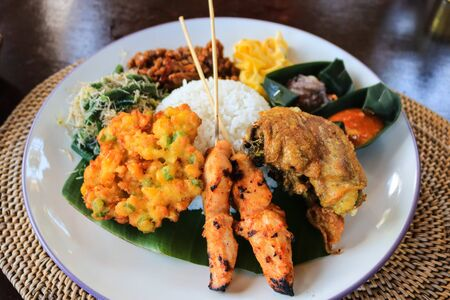 Chicken satay with rice and fried corn, pork, coconut. Traditional food