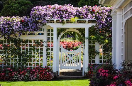 Botanische tuin witte hek met poort en bloeiende bloemen Stockfoto