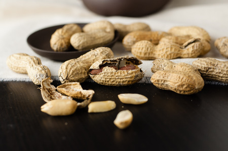 allergic ingredients: Close up peanuts on a small plate and linen  tablecloth Stock Photo