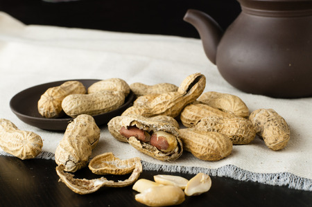 Close up peanuts on a small plate and linen tablecloth with clay teapot