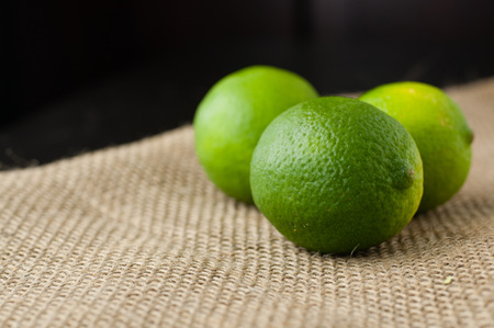 photography background: Green limes on a jute table cloth Stock Photo