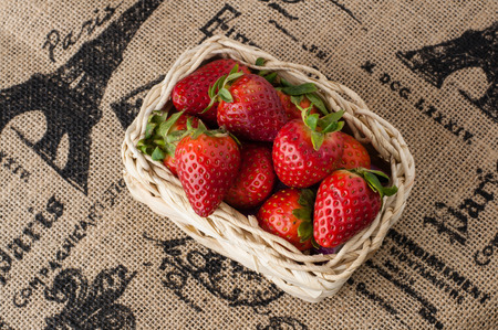 Strawberries in a small basket on jute tablecloth with French motif print