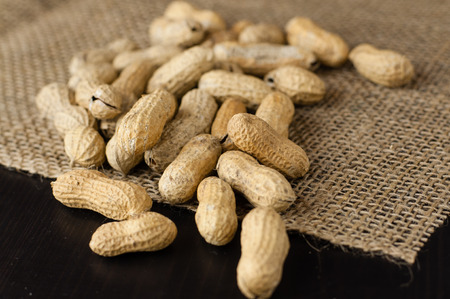 Peanuts in shell on jute tablecloth Stock Photo