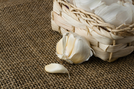 Garlic in a small basket on jute table cloth close up