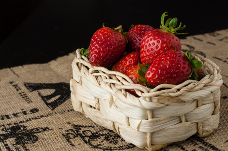 Strawberries in a small basket black background