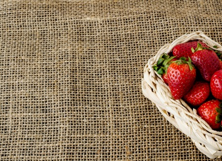 Strawberries in a small basket on a jute tablecloth