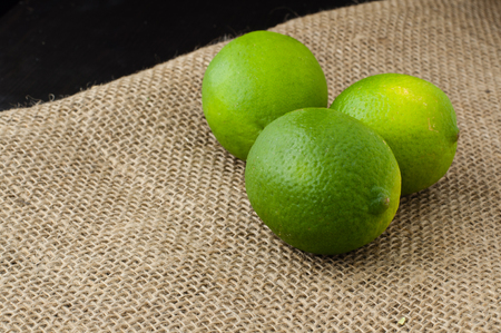 Limes on a beige jute tablecloth