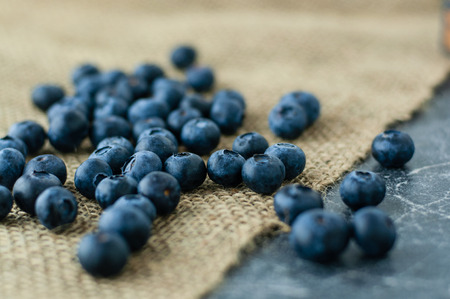 Scattered blueberries on jute tablecloth and scratched black background Stock Photo
