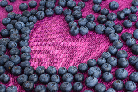 Heart shaped blueberries scattered on a pink jute tablecloth