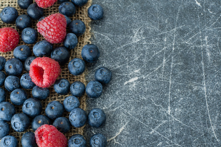 scattered in heart shaped: Blueberries and raspberries scattered on a jute cloth and chalkboard background