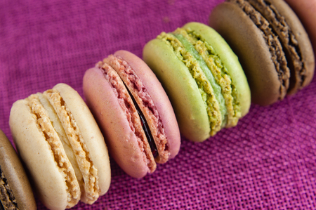 Line of macaroons on pink jute tablecloth closeup