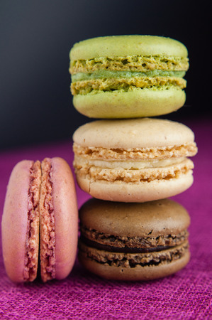 Stack of macaroons on pink jute tablecloth black background closeup Stock Photo