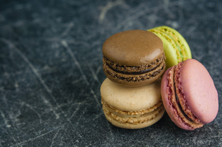 Stack of macaroons on a scratched old chalkboard background, space for text