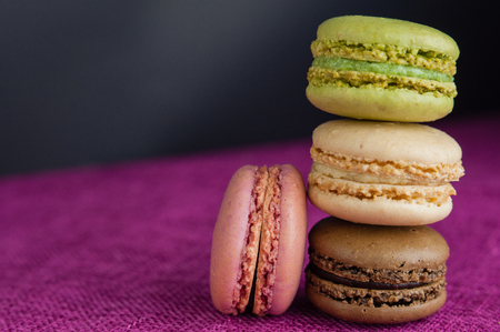 Stack of macaroons on pink jute tablecloth black background