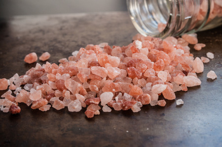 Scattered Himalayan pink salt crystals from glass bottle on rusty metal background Stock Photo