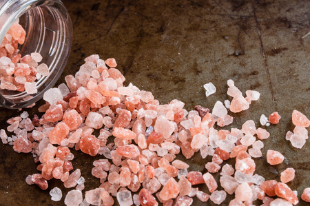 Scattered Himalayan pink salt crystals, top view on rusty metal background Stock Photo