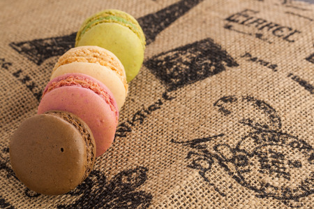 Line of macaroons on the jute tablecloth with space