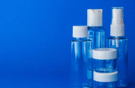 Empty cosmetic plastic transparent bottles on blue background