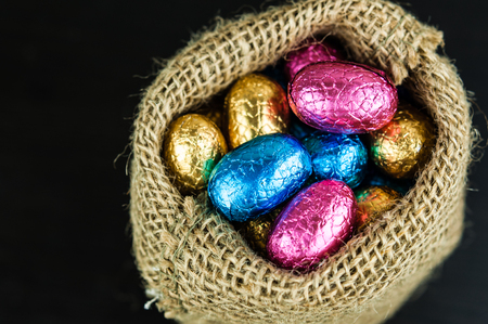 Chocolate Easter eggs in colorful foil in small jute bag on dark background, top view