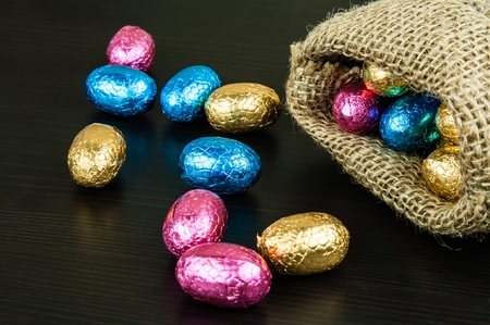 Chocolate Easter eggs in colorful foil on dark background scattered from small jute bag