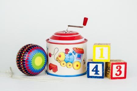 juguetes antiguos: Juguetes viejos de yo-yo, esta�o caja de m�sica zanfona y cubos con n�meros, aislado Foto de archivo