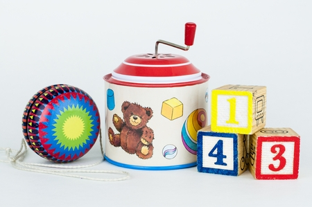 Old toys yo-yo, tin hurdy-gurdy musical box and cubes with numbers, isolated