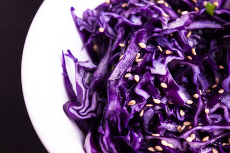 Purple cabbage slaw with sesame seeds, in a white bowl dark background, close up