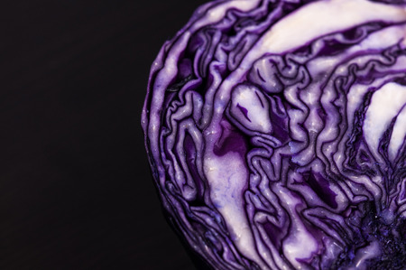 Purple cabbage cut in half dark background, close up space for text Stock Photo