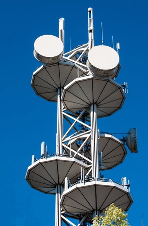 Telecommunication tower in the city against blue sky Stock Photo