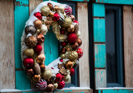 Christmas wreath on a wooden door, outside with snow covered ornaments Stock Photo