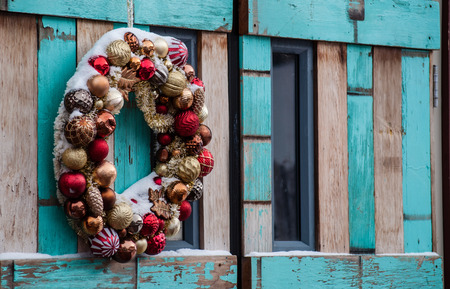 Christmas wreath on a wooden door, outside with snow covered ornaments Standard-Bild
