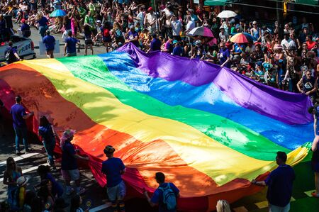 Rainbow flag carried by people collecting donations during pride parade in Vancouver, British Columbia, Canada on August 5th, 2018