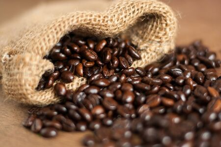 Freshly roasted dark coffee beans out of small jute sack, close up Standard-Bild