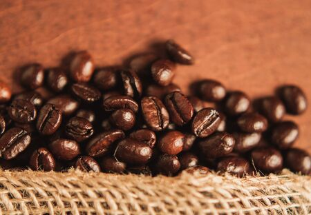 Freshly roasted scattered dark coffee beans, with mood filter, close up
