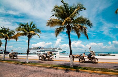 Vintage horse drawn carriages parked along the street and seawall on Cozumel island, Mexico with cruise ship at the background.