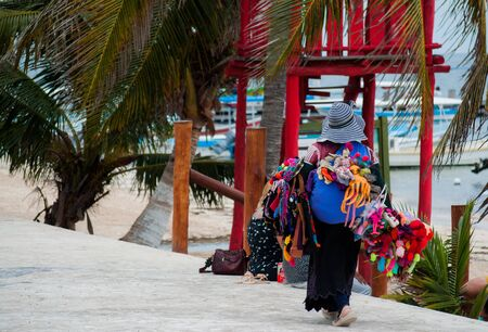 Street vendor woman selling colorful traditional handmade souvenirs near the beach at Puerto Morelos, Mexico