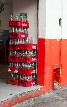 Playa del Carmen, Mexico - August 22, 2019. Empty Coca-Cola bottles in the crates at the entrance of small Mexican street cafe