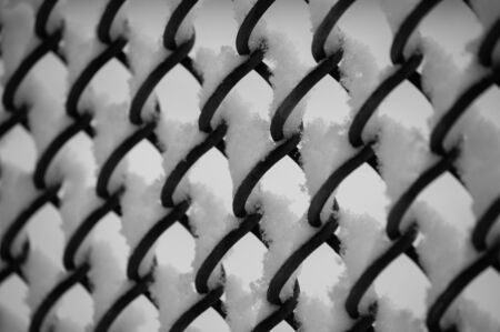Metal mesh fence of a tennis court covered in snow at the Stanley park, Vancouver, Canada