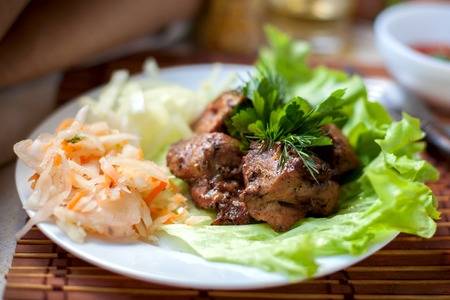 shashlik: grilled shashlik with pickled cabbage and salad and fragrant herb Stock Photo