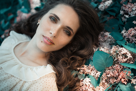 Young girl in soft light style color lie in lilac flowers. beautiful fashion make up. Sun shadow on face