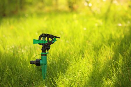 sprinkle system: Plastic garden splinkter standing on the groud in the gazon grass