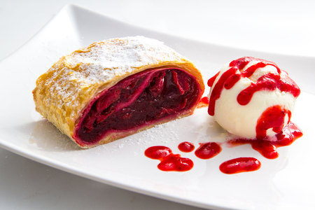 cherry strudel food with icecream on the plate with red syrop isolated on whithe background