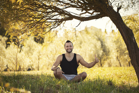 Yoga outdoors in warm autumn park. Sinlight effect. Man sits in lotus position zen gesturing. Concept of healthy lifestyle and relaxation. Young athlete doing OK symbol. Thumb ub