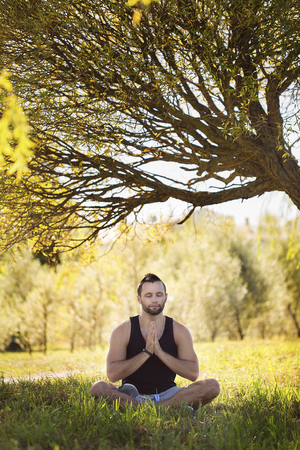 Yoga outdoors in warm autumn park. Sinlight effect. Man sits in lotus position zen gesturing. Concept of healthy lifestyle and relaxation.Young athlete doing exercises.