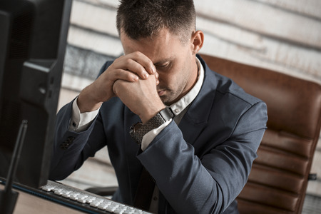 Tired business man at workplace in office holding his head on hands. Sleepy worker early in the morning after late night work. Overworking, making mistake, stress, termination or depression concept Archivio Fotografico